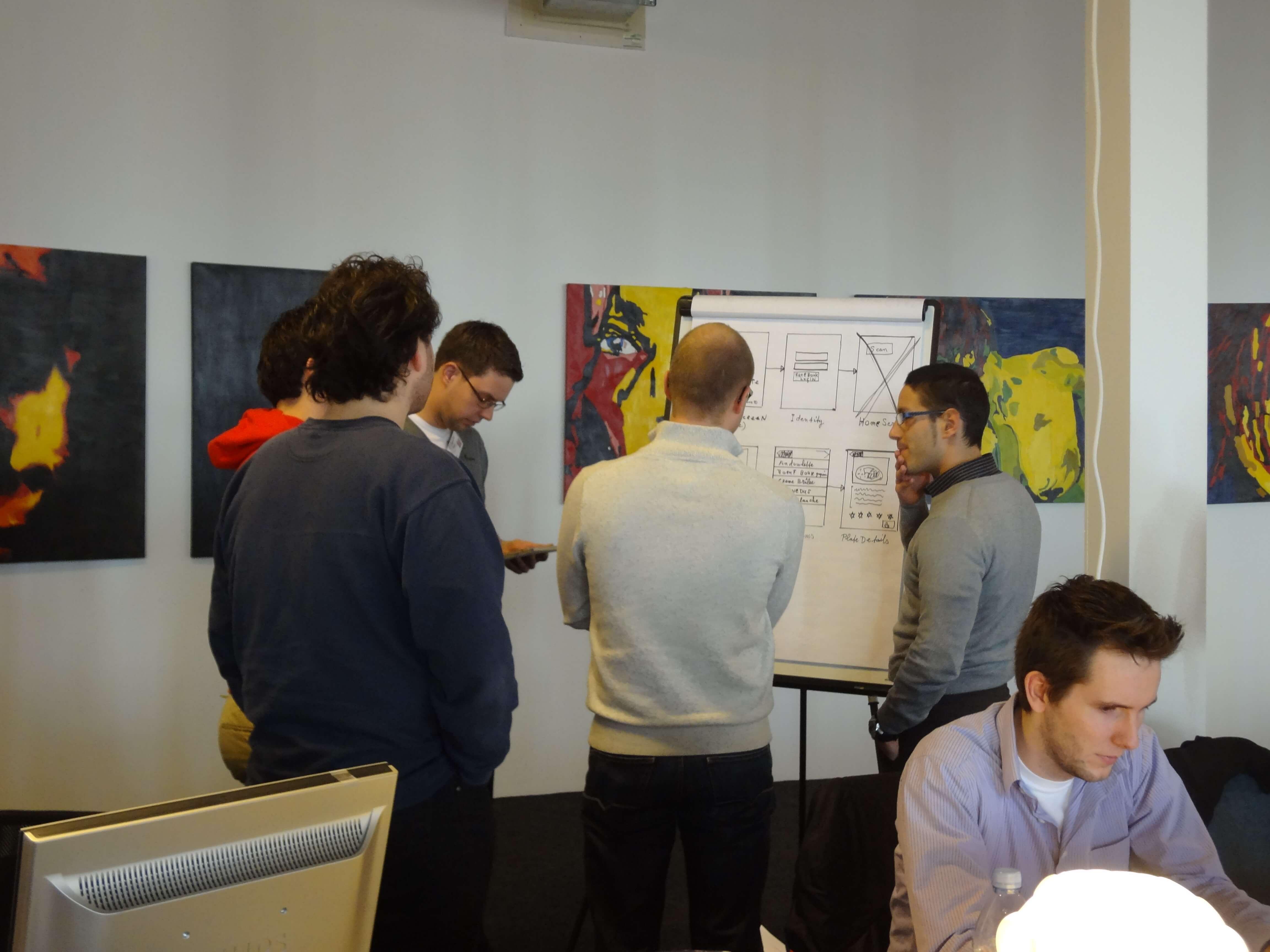 5 mensen voor een whiteboard die overleggen