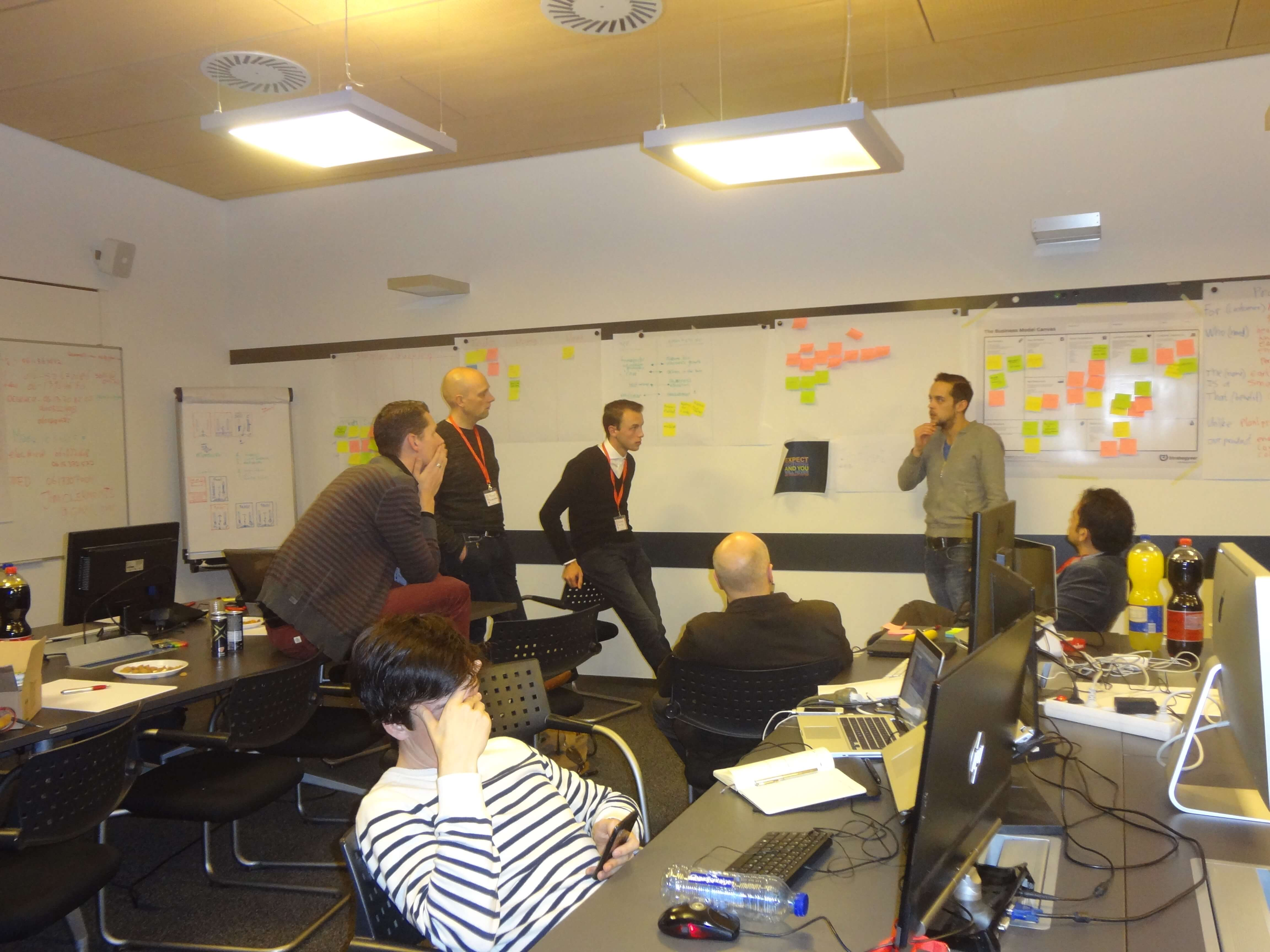 7 mensen die overleggen voor een whiteboard.