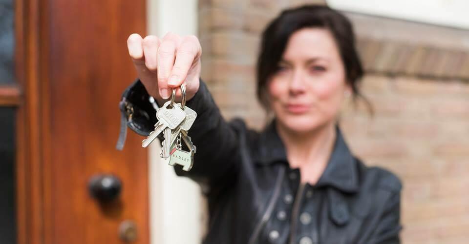 een vrouw met sleutels van haar nieuwe huis