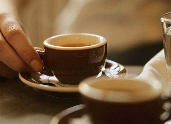 een kop koffie met een hand