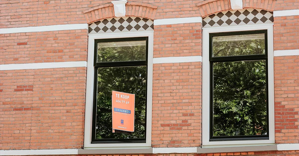 een raam van een huis met een te koop bord