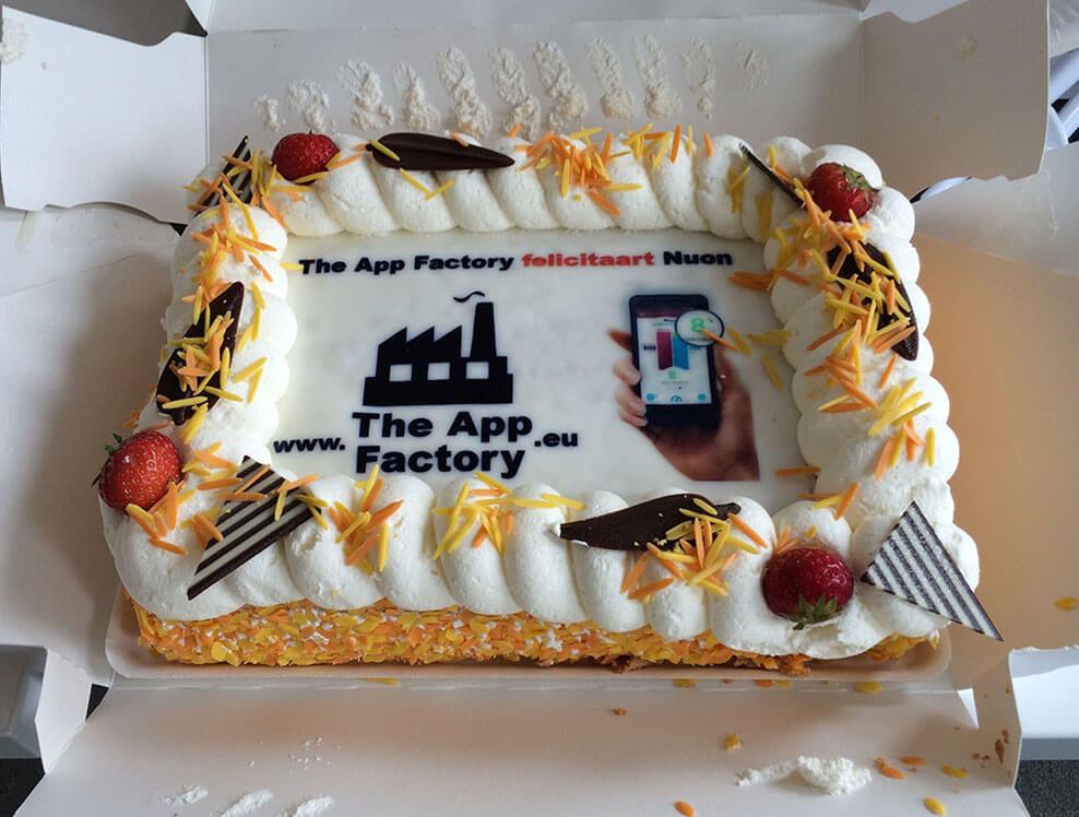Een slagroomtaart met logo van the app factory